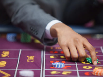 Man in a casino is placing a bet at roulette table
